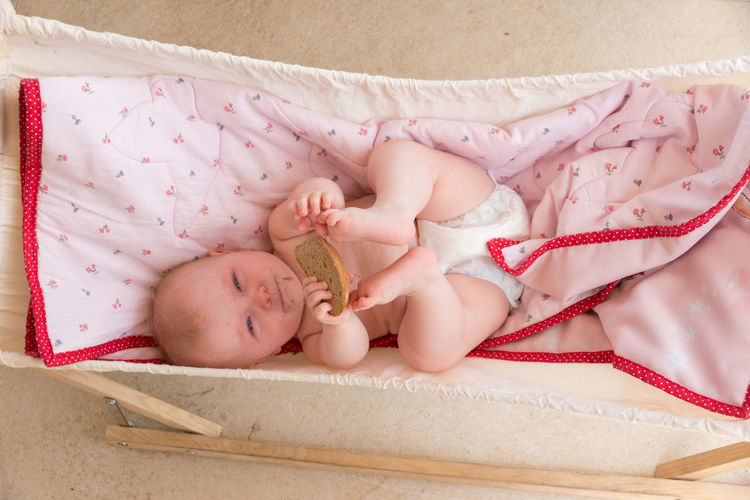european baby with blue eyes and a piece of bread in hammock Caucasian European  Looking At Camera Hammock Day Bread Pink Color View From Above Baby Young Babyhood Child Childhood Real People Innocence Cute One Person Blanket Lying Down Lying On Back Lying Toddler  Lifestyles High Angle View Looking