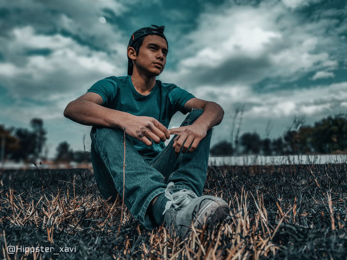 Young man sitting on field