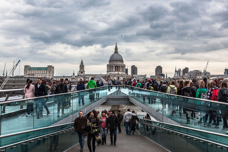 People walking on milennium bridge against st. paul's cathedral
