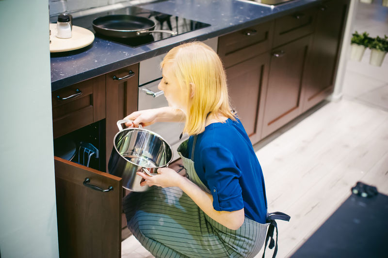 Side view of young woman working in kitchen