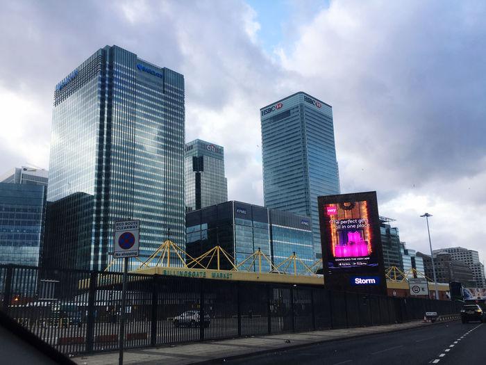 Modern buildings by road against sky in city