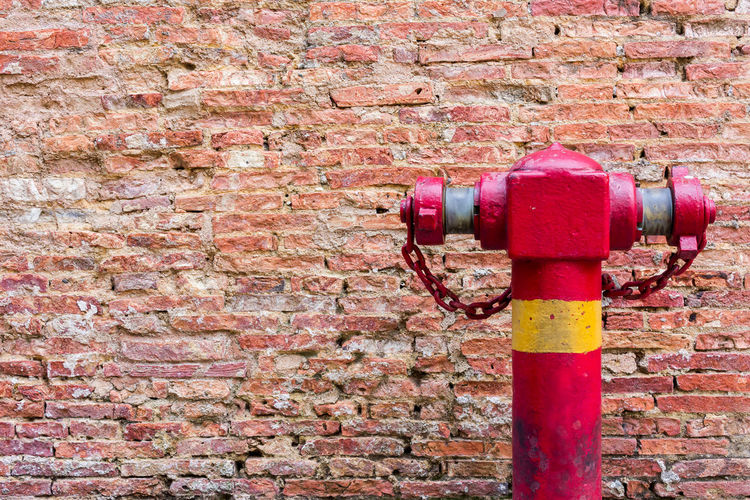 Fire Hydrant at the Weathered stained old dark brown Wall, Dirty Brick Wall Brick Wall Day Emergency Extinguish Fire Fireman Hose Hydrant No People Outdoors Red Safety