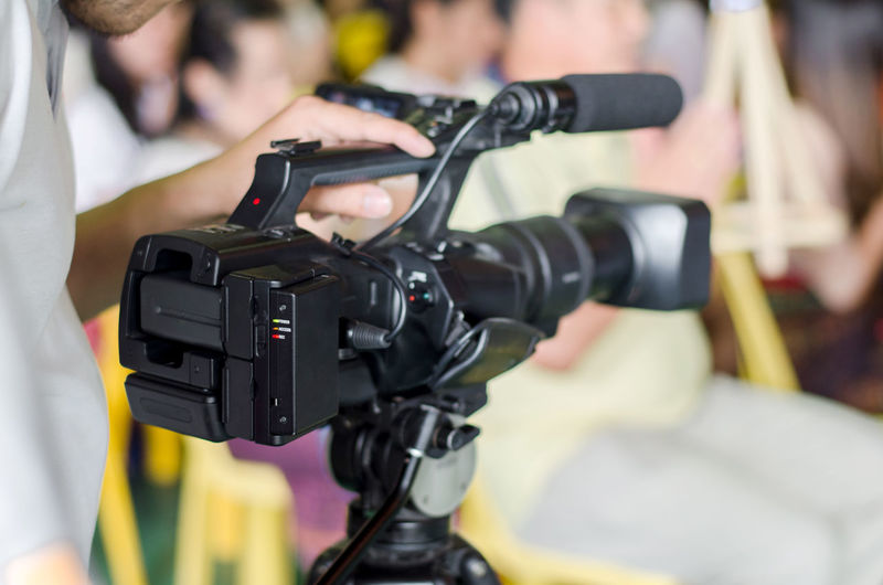 Cropped hand operating camera during event