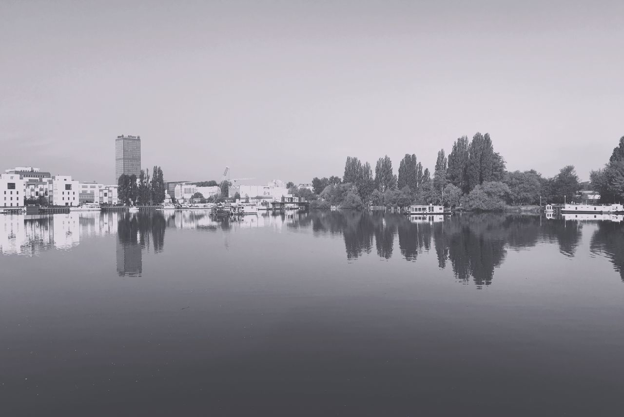 Reflection Of Buildings In Water Against Clear Sky