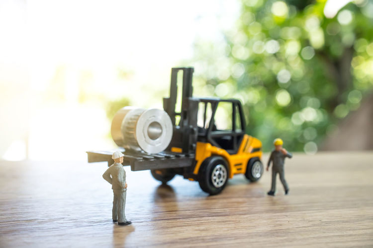 Close-up of figurines with toy forklift on table