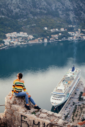 Woman relax sitting on high angle panoramic view with mountains and Bay. Authentic Moments EyeEm Best Shots Panoramic Relaxing Sitting Travel Woman Adult Adventure Aerial View Bay Casual Clothing Chatting Communication Cruise High Angle View Montenegro One Person Outdoors Picturesque Sexygirl Smart Phone Sunglasses
