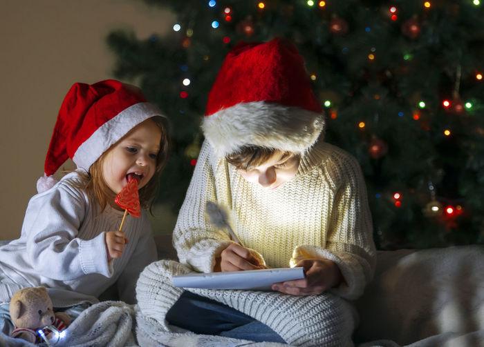 Full length of girl sitting on christmas tree