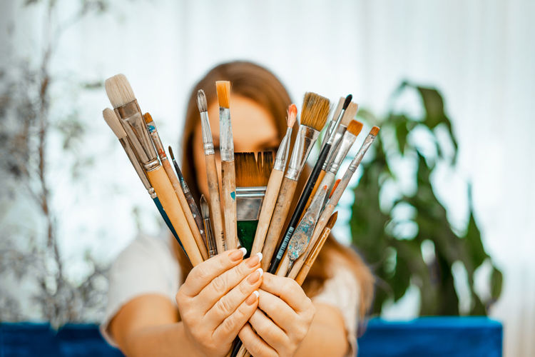 Close-up of woman holding paintbrushes