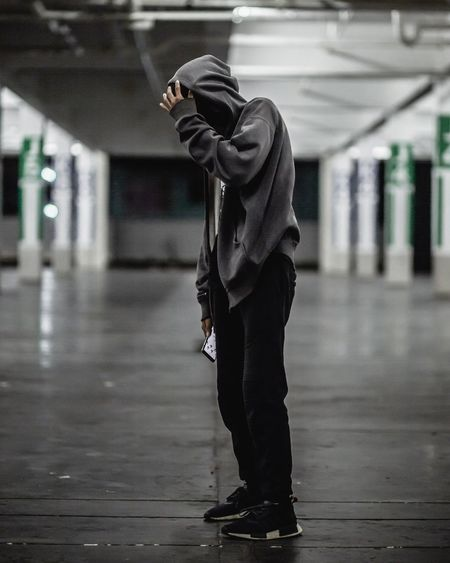 Full length of man wearing hooded jacket while holding in parking lot
