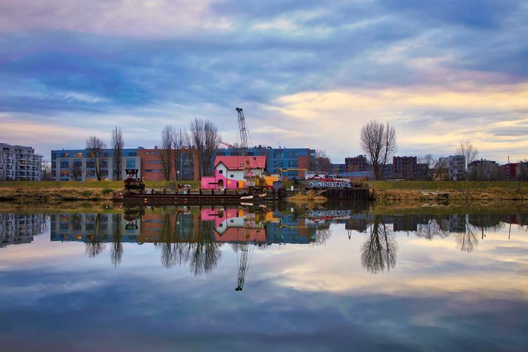 Reflection of buildings in river against sky
