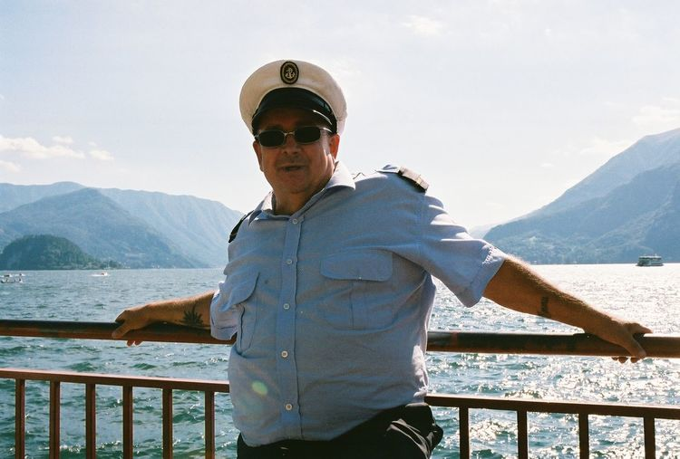 Boat captain standing by railing against sky