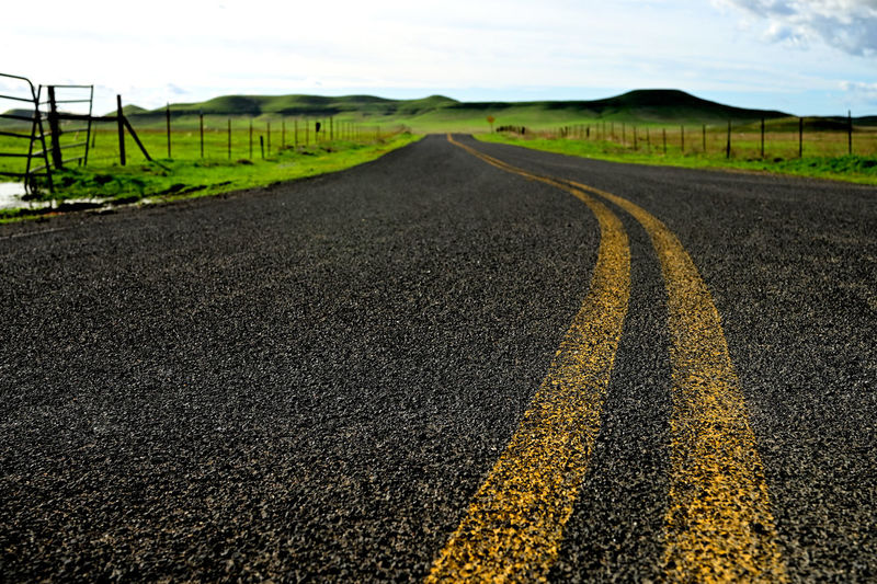 Surface level of road amidst land against sky