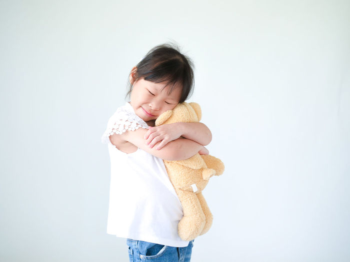 Smiling Embracing Teddy Bear While Standing Against White Background