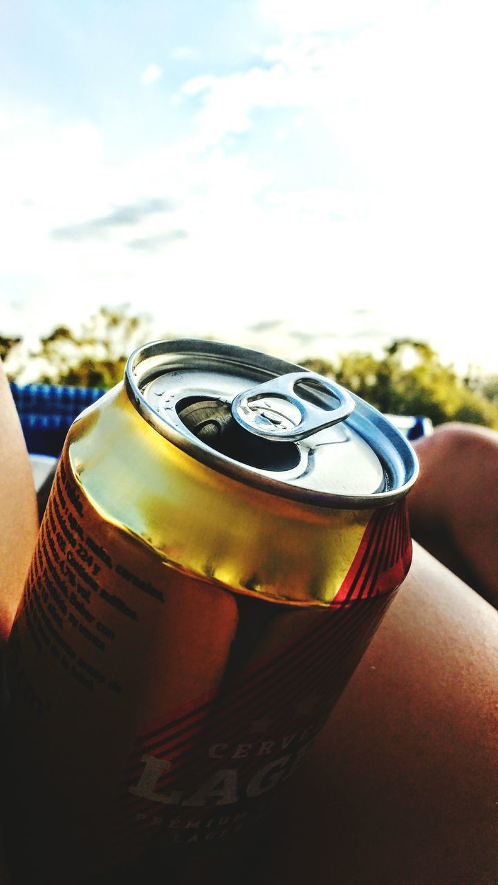 food and drink, close-up, focus on foreground, drink, day, outdoors, can, human hand, sky, one person, people