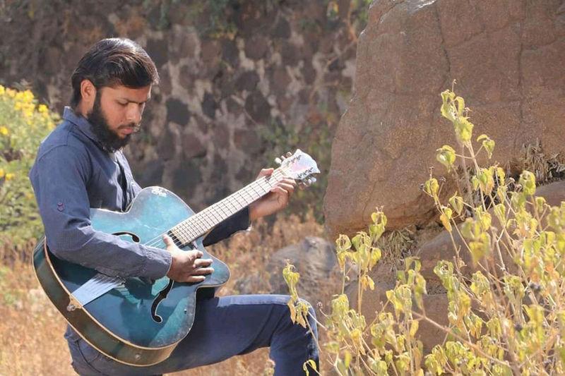 Young man playing guitar against plants