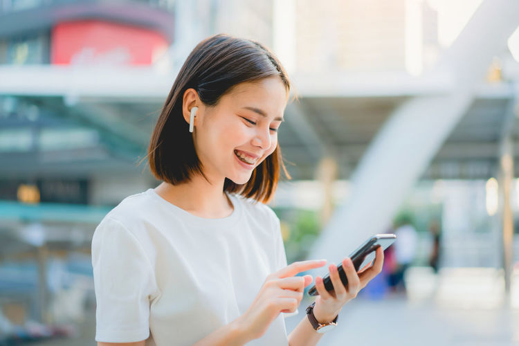 Smiling young woman using mobile phone outdoors