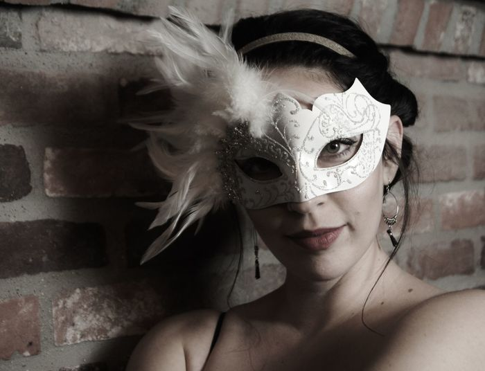 Portrait of young woman wearing mask by brick wall