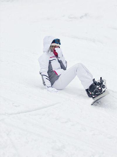 Woman snowboarding on snowy field