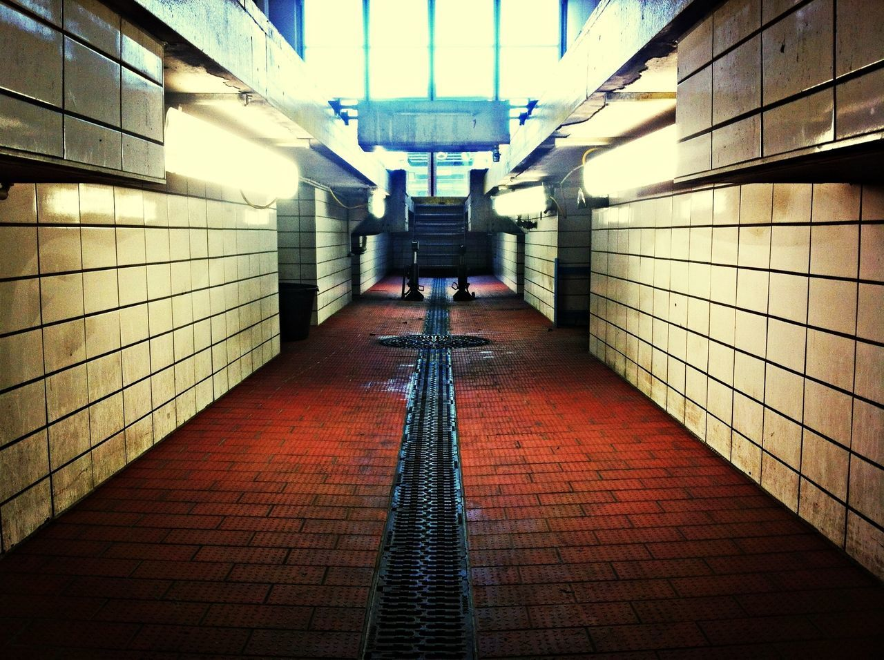 Empty walkway with tiled walls in subway