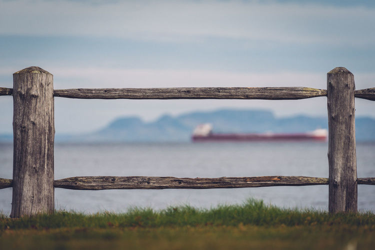 Wooden railing on grass by sea against sky