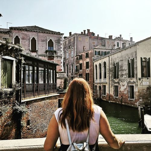 Rear view of woman with buildings against sky