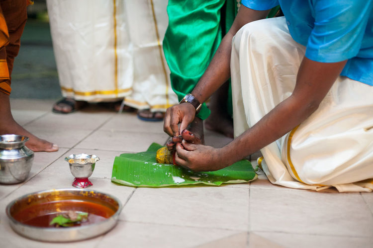 Midsection of man putting jewelry on bride foot during wedding ceremony