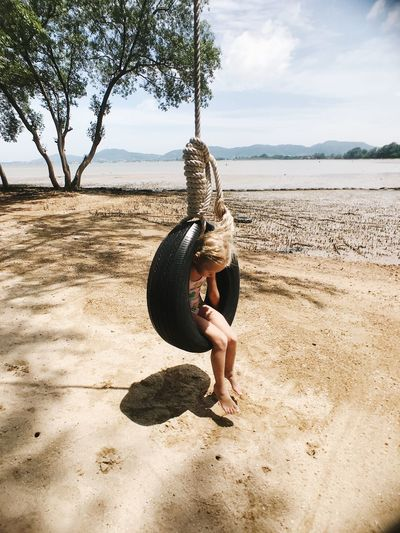 Full length of girl sitting in tire swing at beach against sky