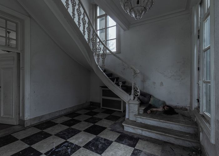 Unconscious woman lying on staircase in abandoned home