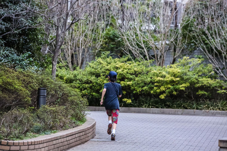 Rear view of girl jogging in park