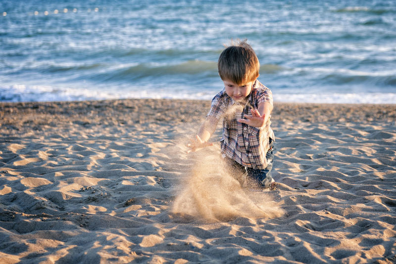 Boy Playing With Sand At Beach During Sunset
