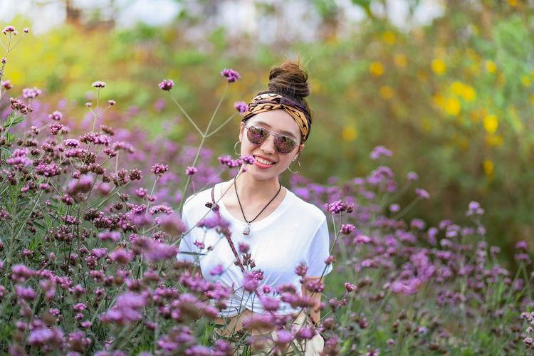 Portrait of smiling woman by purple flowering plants