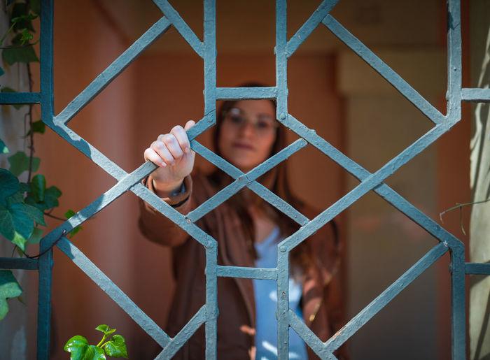 Portrait of woman looking through metal grate