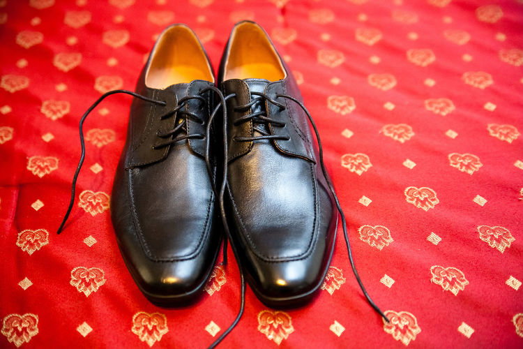 Close up pair of men's untied formal black shoe's sitting on read carpet. Wedding Wedding Shoes Black Color Black Shoes Close-up Day Fashion Footwear Formalwear High Angle View Indoors  Men's Footwear Mens Fashion Menswear No People Pair Red Red Floor Shoe Untied Shoelaces First Eyeem Photo