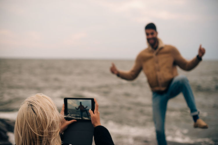 People photographing sea through smart phone on beach