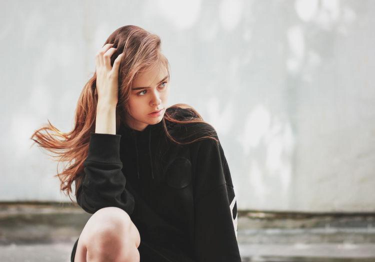 Beautiful young woman crouching outdoors