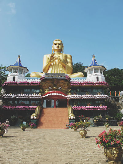 Large gold statue of buddha on top of temple
