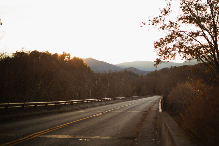 Empty road along trees and mountains against clear sky