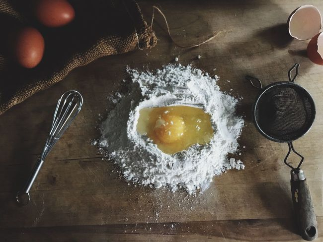 Fresh ingredients flatlay. Egg in flour and sifter Flour Food And Drink Preparation  Indoors  Food Egg Dough Table Freshness Rolling Pin High Angle View IPhoneography Egg Yolk Close-up Day Eggs Raw Egg Raw Ingredients Ingredient Flatlay Flat Lay Sifter Wisk Farm Eggs Brown Eggs