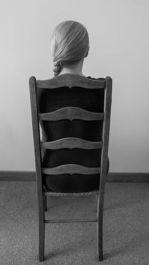 Rear view of woman sitting on chair against wall