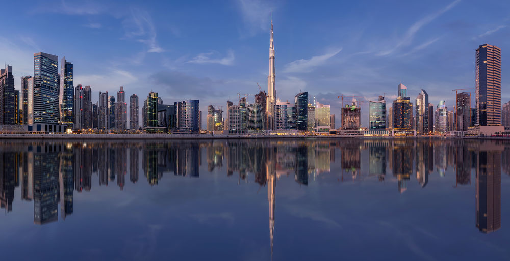 Reflection of modern buildings on river against sky in city