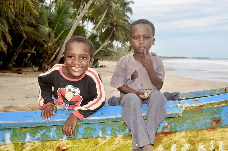 Portrait of brothers on boat at beach