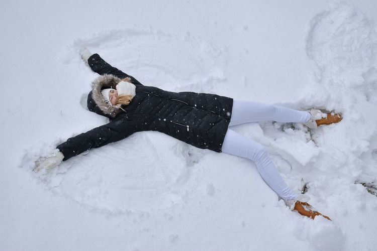 Young woman in black coat playing with snow