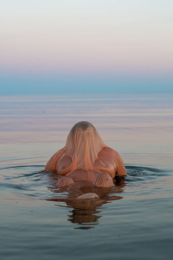 Midsection of woman by sea against sky during sunset