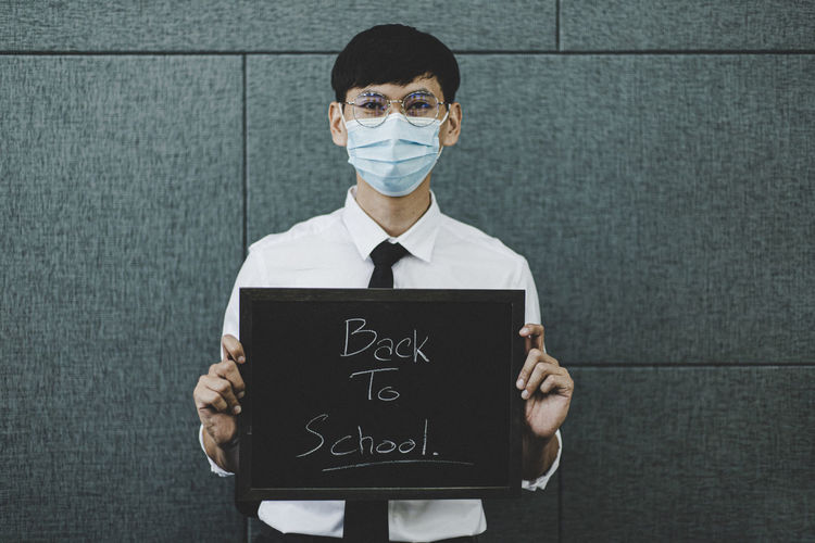 Portrait of man wearing flu mask holding slate against wall