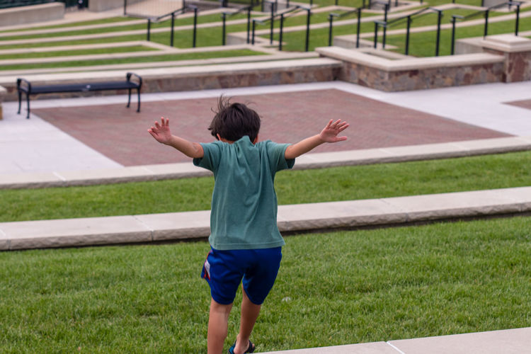 Rear View Of Boy Jumping On Field