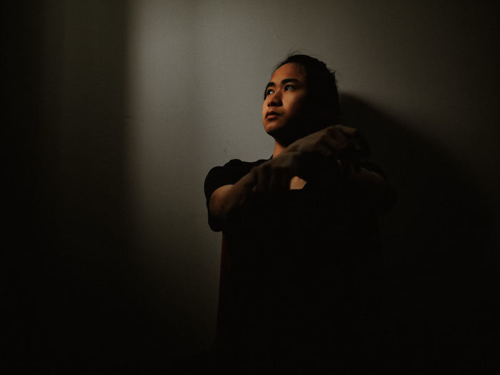 Young man looking away while standing against black background