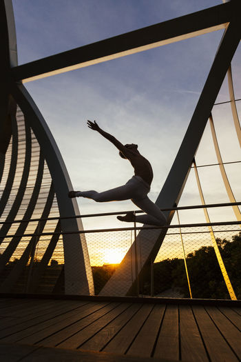 Side view of shirtless man jumping on footbridge during sunset