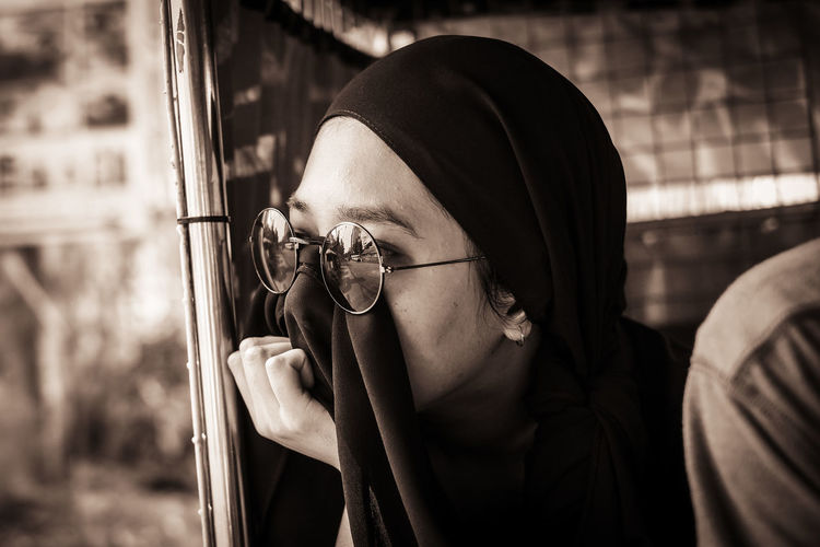Close-up of young woman wearing hijab looking away in vehicle