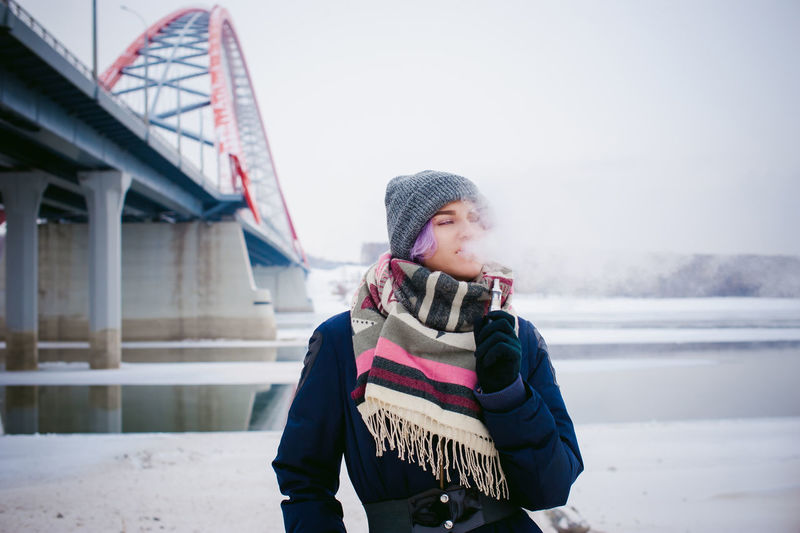 Young woman smoking while standing by bridge against sky during winter