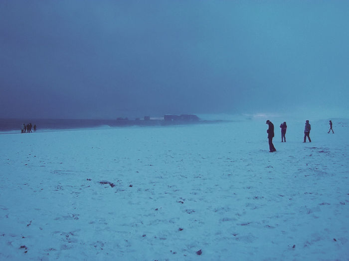 People on sea shore against sky during winter
